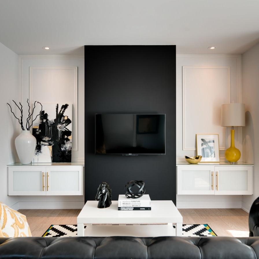 دکوراسیون داخلی نشیمن مدرن و کوچکی که برای تاکید به نقطه کانونی آن، دیوار پشت تلویزیون را به رنگ مشکی نقاشی کرده اند