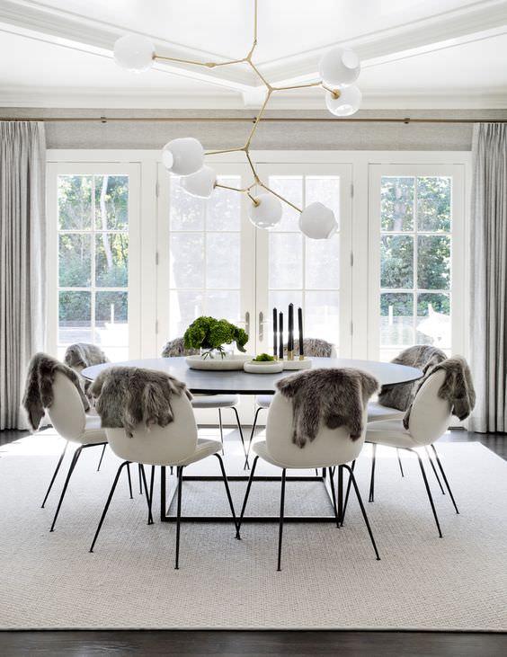 طراحی و دکوراسیون اتاق ناهار خوری با لوستر شاخه ای که از تعادل شعاعی برای چیدمان صندلی و میز در آن استفاده شده است