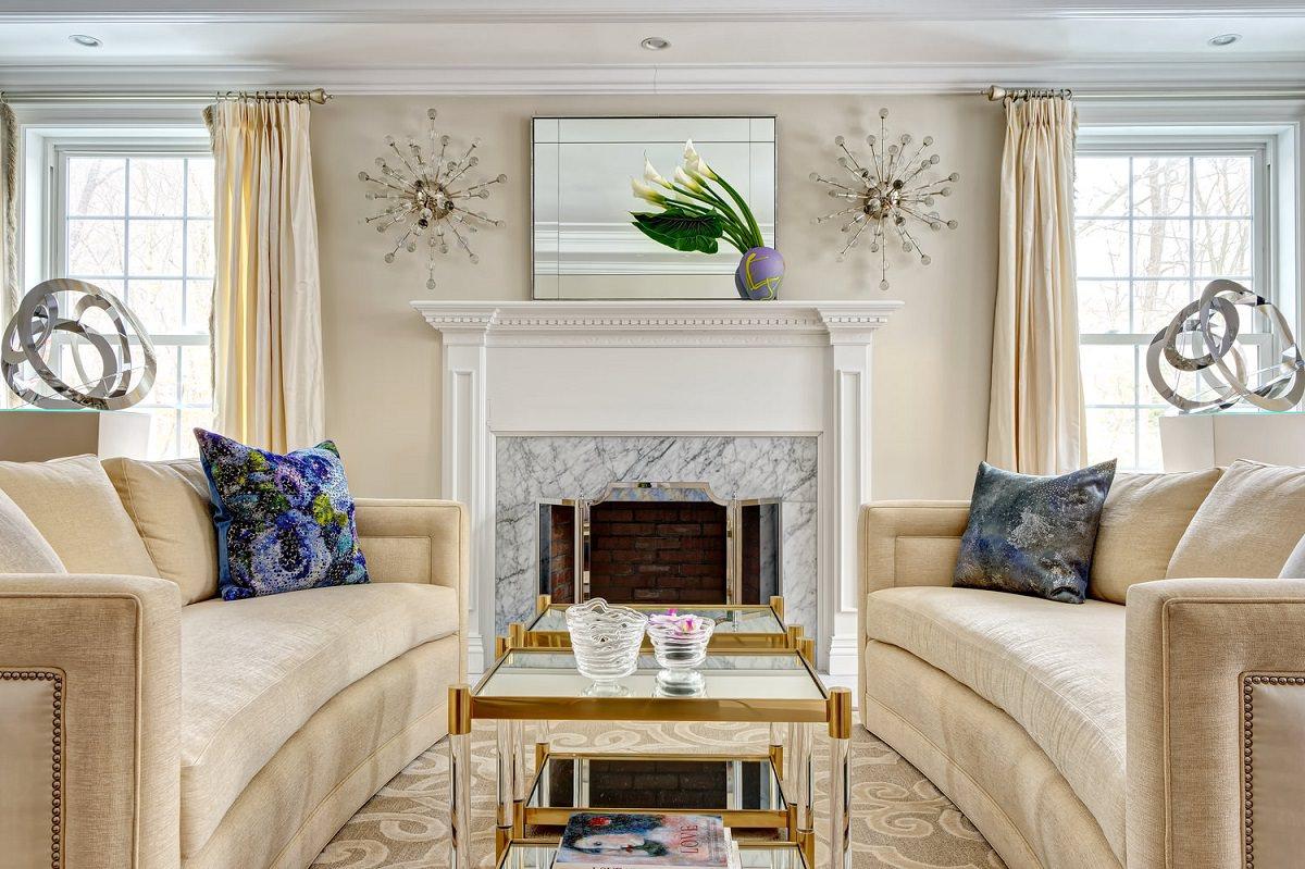 دکوراسیون داخلی اتاق پذیرایی کلاسیک و لوکس با مبل، دیوار و پرده های کرم که در آن تعادل متقارن ایجاد شده است