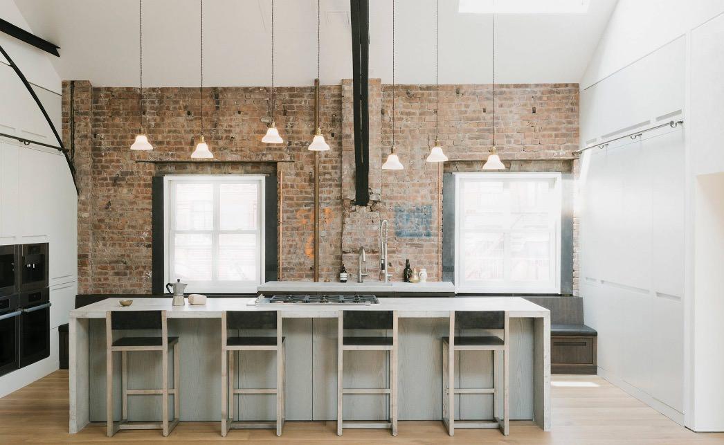 طراحی داخلی آشپزخانه مدرن با دیوارهای آجری که از چندین آویز کوتاه و بلند برای به وجود آوردن ریتم در آن استفاده شده است