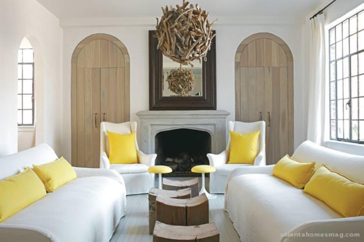 دکوراسیون سالن پذیرایی با مبل سفید و کوسن زرد که برای ایجاد هارمونی خطوط منحنی و متریال های چوبی در آن تکرار شده است