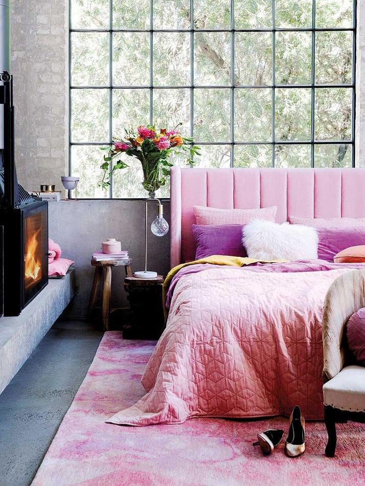 تخت خواب صورتی که به عنوان نقطه کانونی جلو پنجره و دیوار اصلی قرار گرفته است