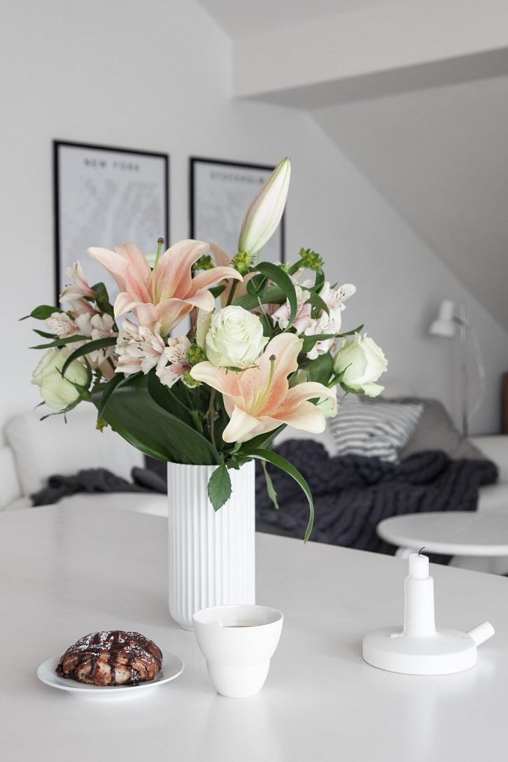 گل های مصنوعی سفید و صورتی در گلدان سرامیکی سفید که با شاخ و برگ طبیعی دیزاین شده است