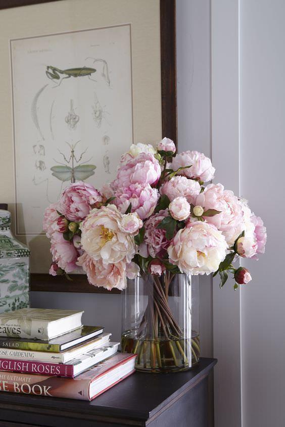 گل های مصنوعی صورتی در گلدان شیشه ای که ساقه انعطاف پذیر دارند