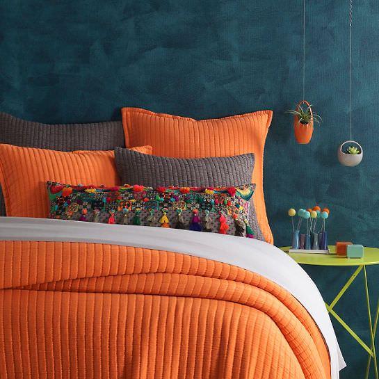اتاق خواب با کاغذ دیواری سرمه ای و روتختی نارنجی