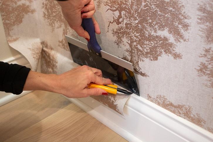بریدن قسمت های اضافی کاغذ دیواری بعد از نصب روی دیوار