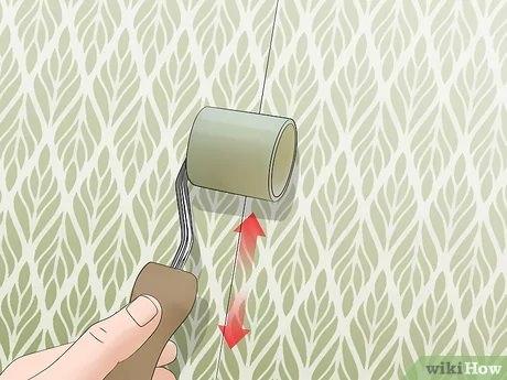 کشیدن غلتک برای از بین بردن درز کاغذ دیواری