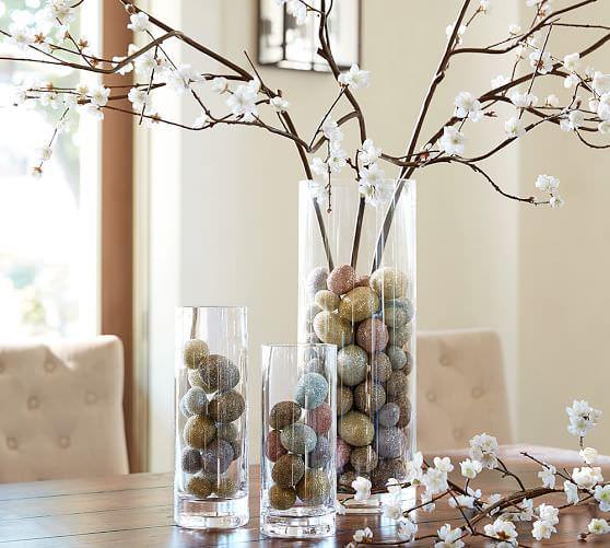 گلدان استوانه ای شیشه ای که در آن شاخه شکوفه مصنوعی و تخم مرغ های تزئینی قرار داده شده است