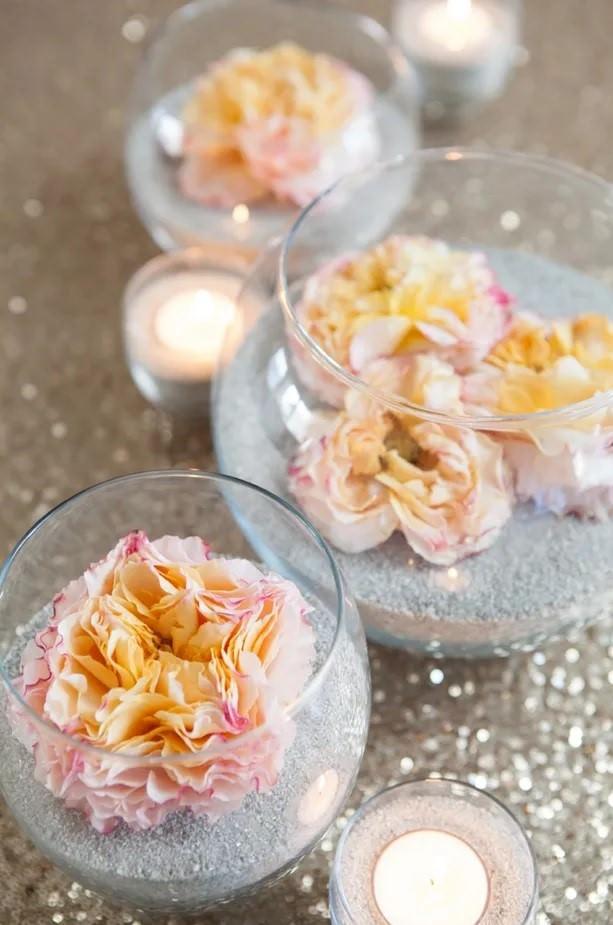 استفاده از ماسه و شن برای تزیین ظرف شیشه ای تنگی با گل مصنوعی