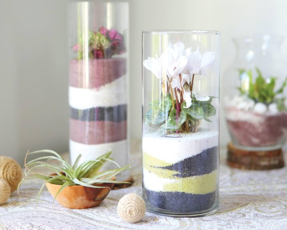 ظرف استوانه ای شیشه ای با شن های رنگی که گل های مصنوعی در آن قرار دارد