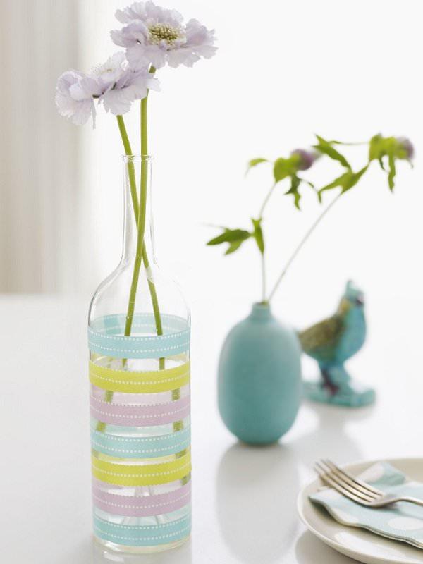 ظرف شیشه ای با گل مصنوعی که با چسب های تزئینی رنگی دیزاین شده است