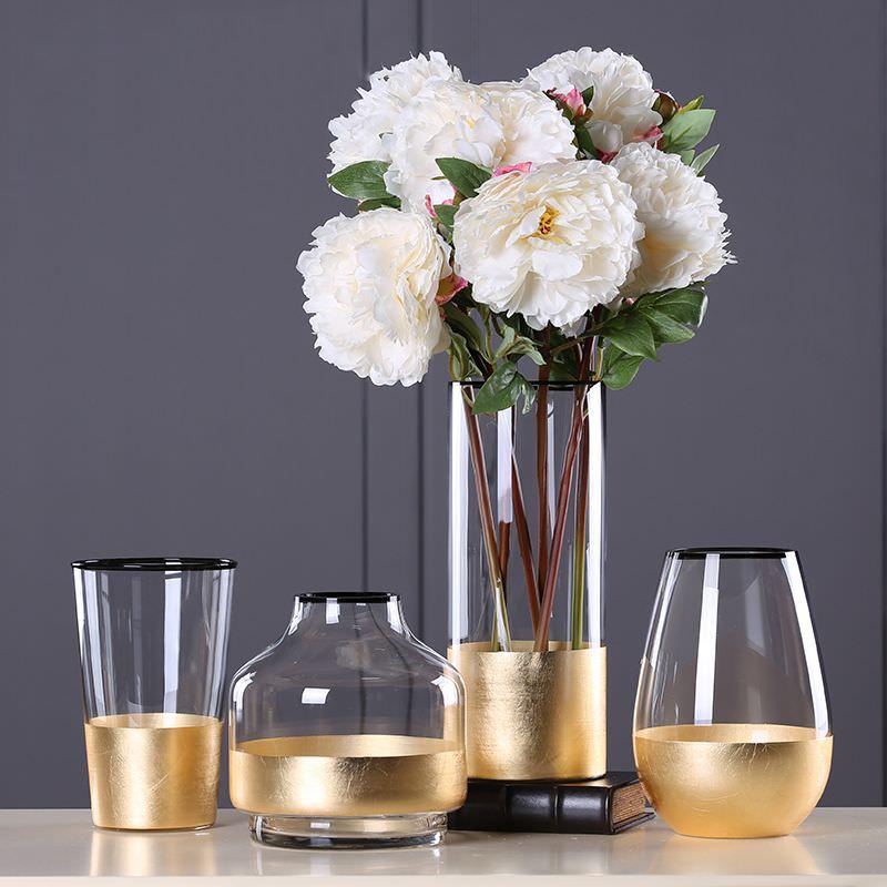 تزئین گلدان شیشه ای با گل مصنوعی که دور آن ورق طلایی چسبانده شده است