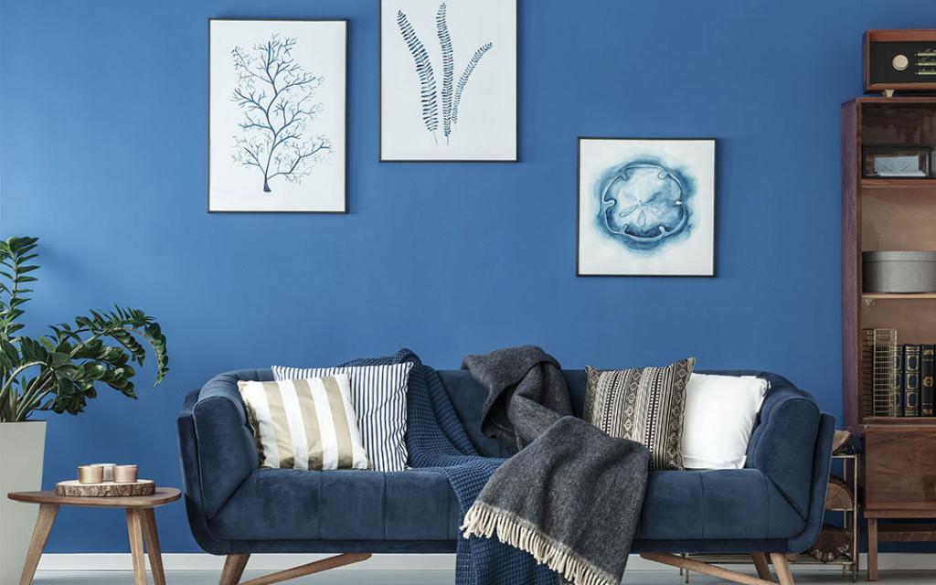 طیف های تیره و روشن آبی در دیوار، مبل و تابلوهای دکوری که رنگ سفید و قهوه ای در کنار آن ها به کار رفته است
