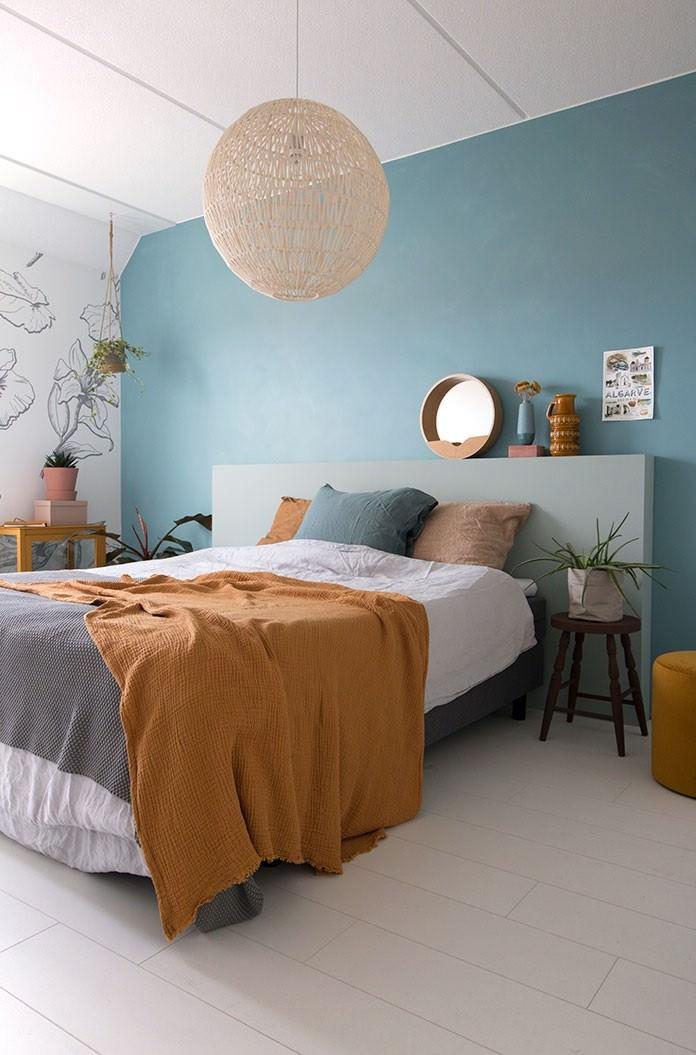 دکوراسیون آبی و زرد اتاق خواب که دیوار تاکیدی آن آبی و اکسسوری و روتختی زرد دارد