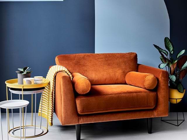 دکوراسیون نشیمن با دیوارهای آبی و مبل تک نفره نارنجی