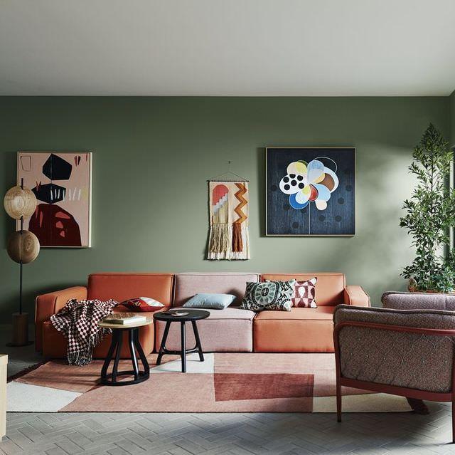 دکوراسیون سبز رنگ دیوارهای نشیمن که مبل و فرش نارنجی در آن استفاده شده است