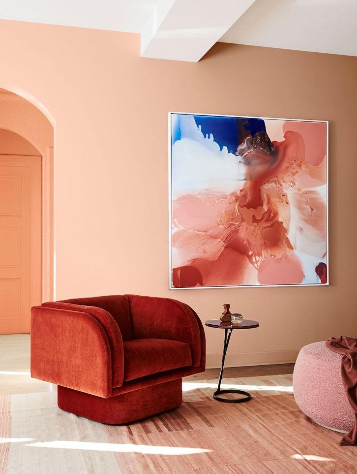 دکوراسیون نارنجی نشیمن که دیوارهای گلبهی و مبل تک نفره نارنجی رنگ و پاف صورتی دارد