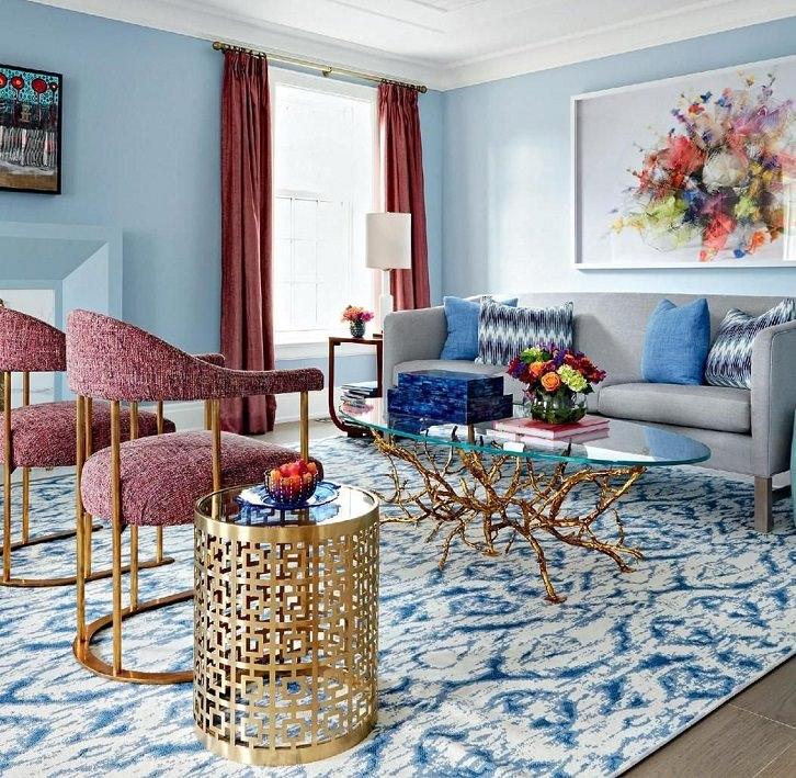 دکوراسیون آبی نشیمن که مبل و پرده قرمز و تابلو دکوری با رنگ های متضاد آبی دارد