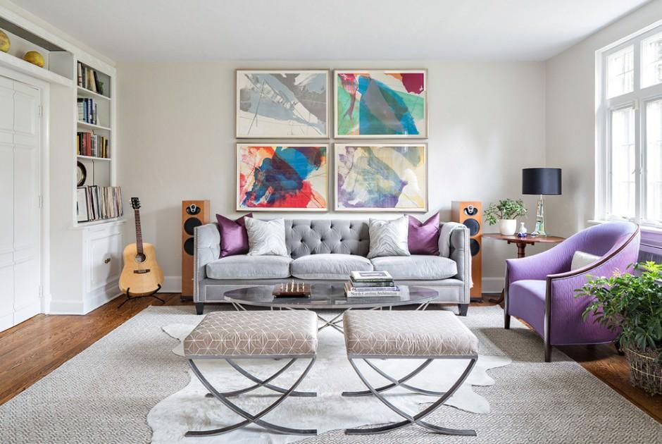 دکوراسیون سفید نشیمن با دیوار سفید و مبل خاکستری و کوسن و مبل تک نفره بنفش که در آن تابلو دکوری رنگارنگ نصب شده است