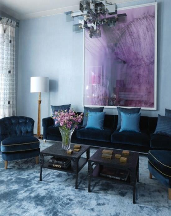 نشیمن با دیوار و مبلمان آبی که تابلو دکوری بنفش روی دیوار آن نصب شده است