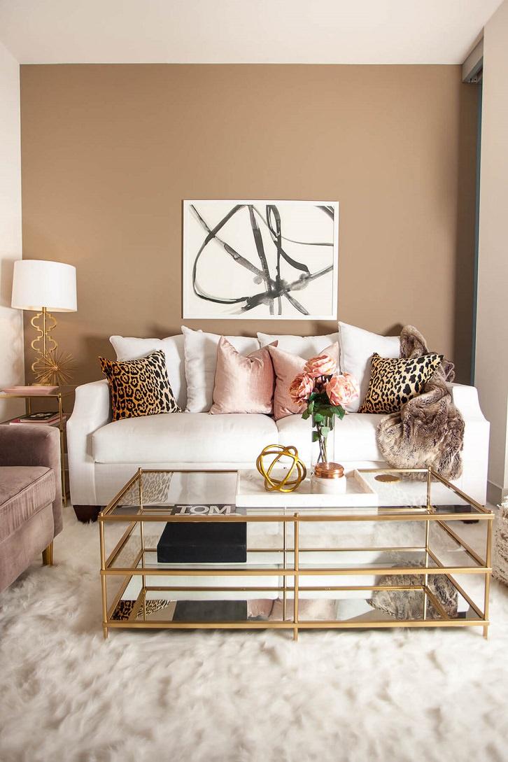 رنگ خنثی بژ در دیوارهای نشیمن که مبل سفید، میز و آباژور طلایی و کوسن های پلنگی و صورتی دارد