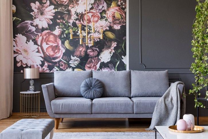 رنگ خنثی خاکستری در دکوراسیون نشیمن با مبل های خاکستری، کفپوش چوبی و کاغذ دیواری گلدار صورتی