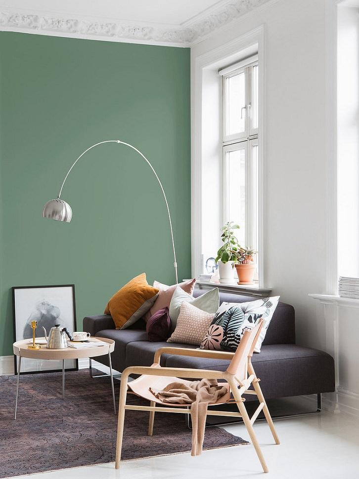 دکوراسیون سفید نشیمن با دیوار تاکیدی سبز که مبل خاکستری مدرن و کوسن های رنگی دارد