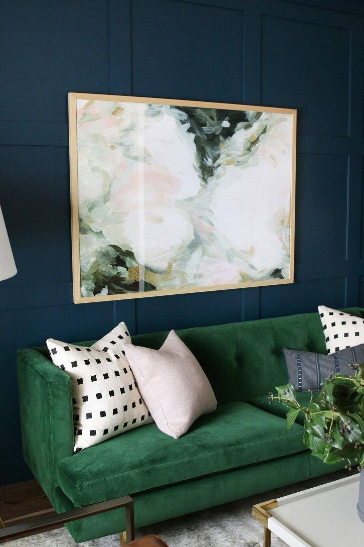 مبل سبز و دیوار آبی تیره که روی آن کوسن های سفید چیده شده است