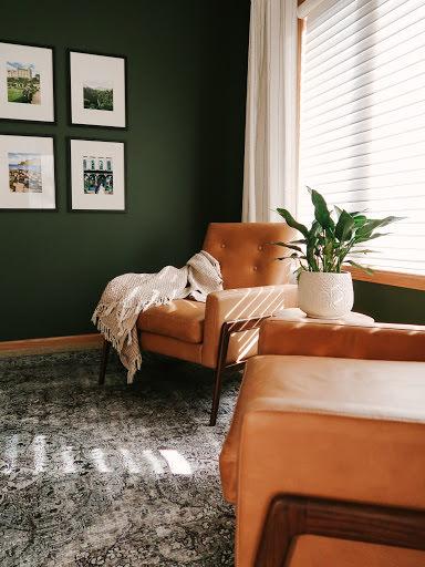 رنگ سبز دیوارهای نشیمن که مبل های تک نفره چرمی قهوه ای دارد