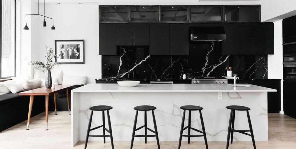 دکوراسیون سیاه و سفید آشپزخانه که کابینت ها در آن سیاه است و جزیره آن از سنگ سفید مرمر است