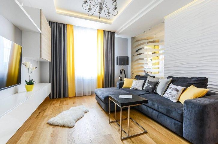 دکوراسیون نشیمن با رنگ دیوار سفید، مبلمن طوسی و کف چوبی که پرده و کوسن زرد دارد