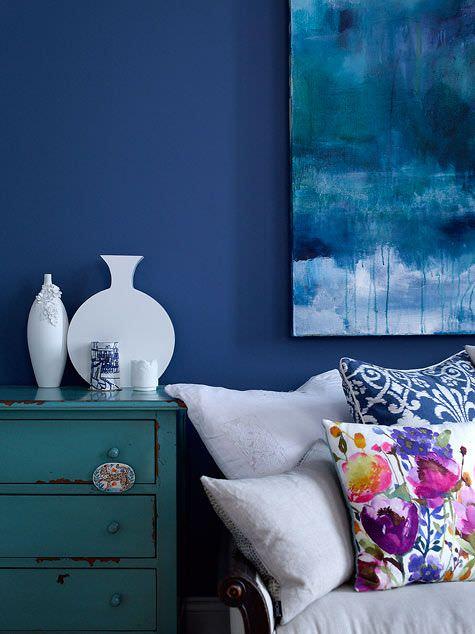 دیوار آبی تیره، کنسول آبی فیروزه ای و کوسن های آبی ارغوانی در دکوراسیون نشیمن