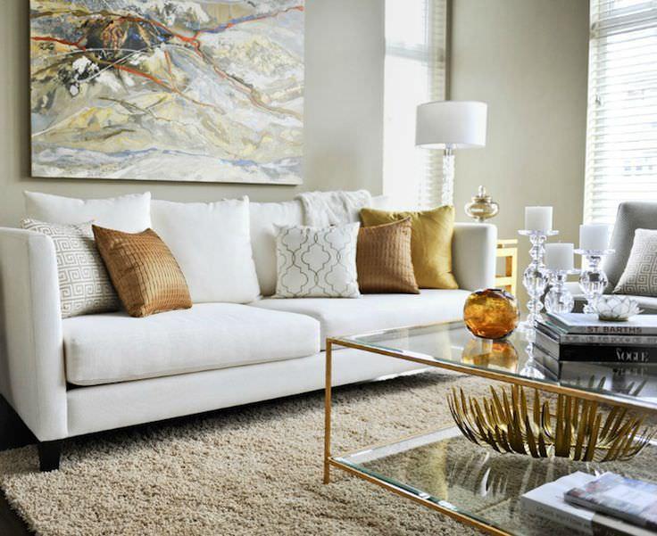 کوسن های طلایی و قهوه ای مبل سفید که با میز جلو مبلی و تابلو دکوری هماهنگی دارند