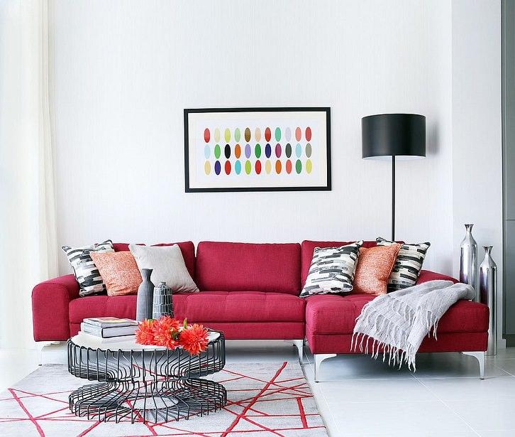 مبل قرمز ال که در نشیمن مدرن با دیوارهای سفید چیده شده است