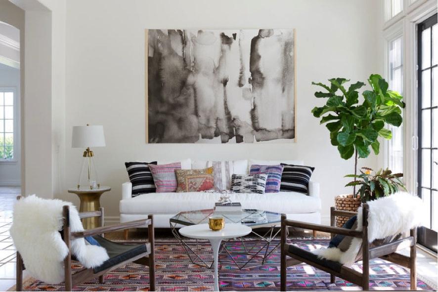 کوسن های رنگی مبل سفید که رنگ و طرح آن ها با فرش هماهنگی دارد