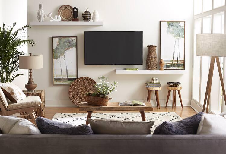 نقاشی دیوار پشت تلویزیون به رنگ خنثی سفید که با شلف و تابلو دیزاین شده است