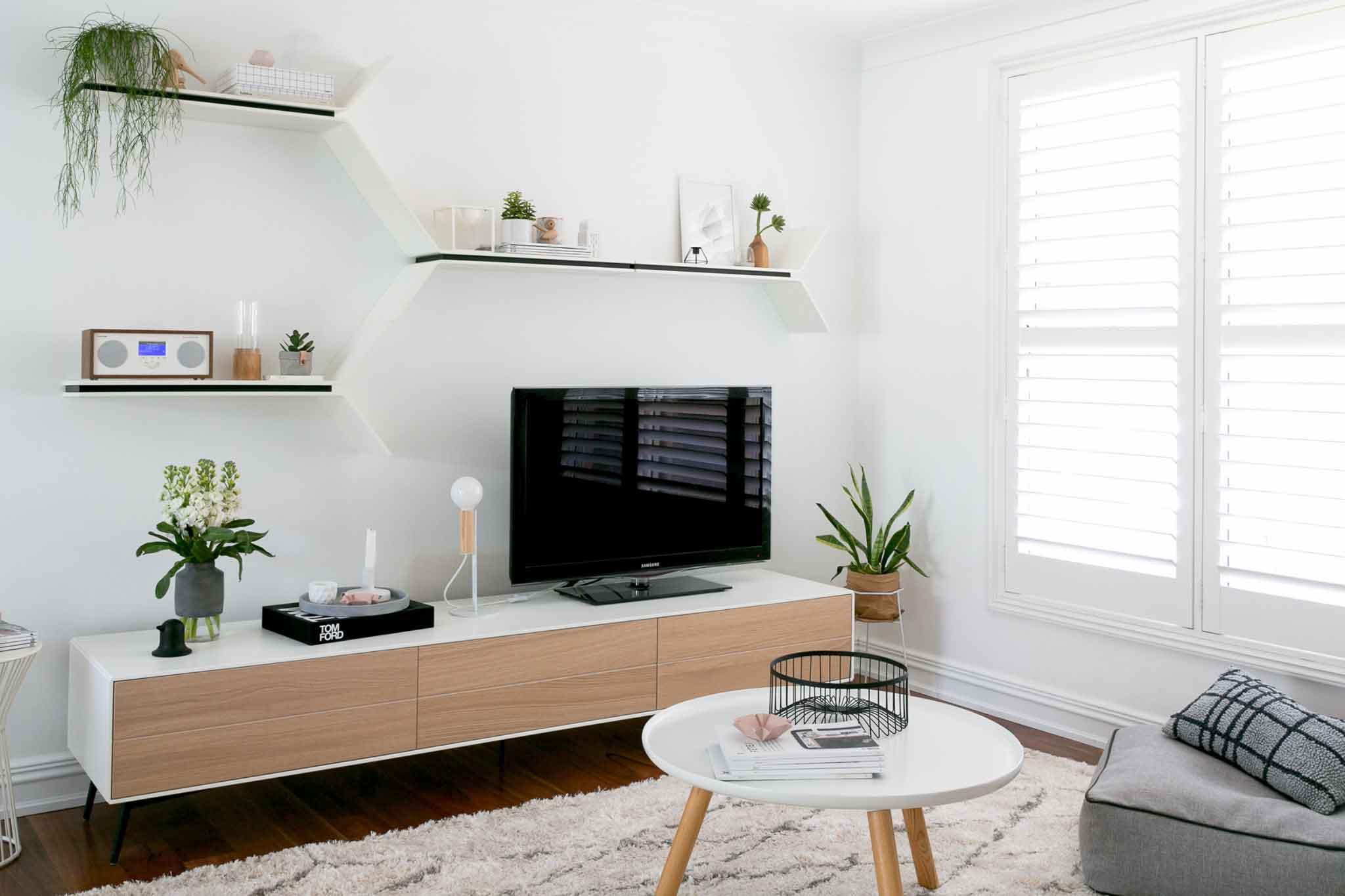 تزیین دیوار پشت تلویزیون با شلف دیواری سفید و مدرن که قاب عکس و گلدان روی آن قرار دارد