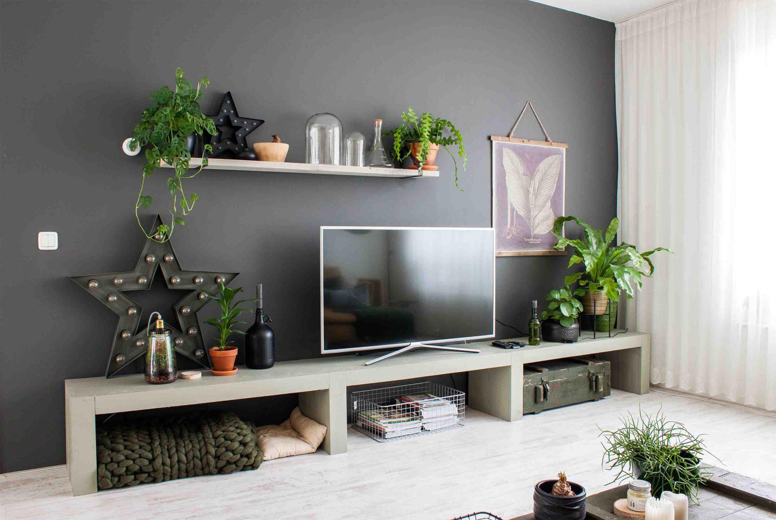 دیزاین دیوار پشت تلویزیون با شلف چوبی، قاب عکس و گلدان