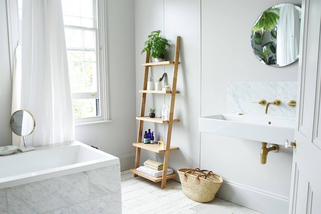 تزیین دیوار حمام و دستشویی با استند نردبانی که گلدان و حوله روی ان چیده شده است