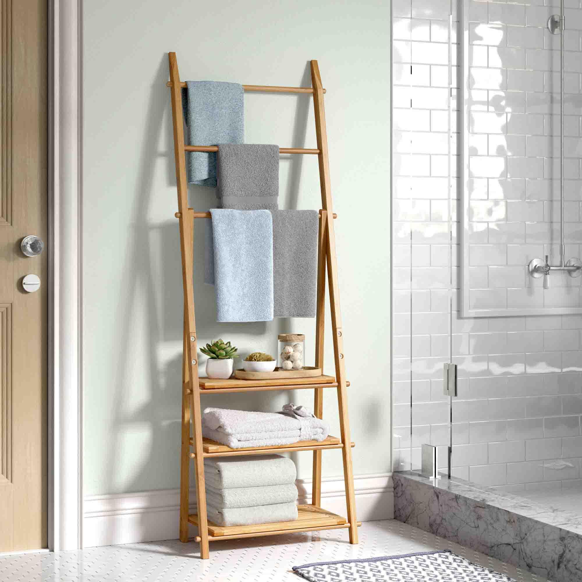 تزیین دیوار دستشویی و حمام با استند نردبانی که روی آن حوله و گلدان چیده شده است